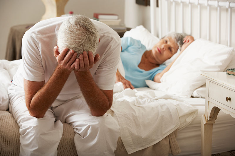 Frustrated Older Man with Sleeping Wife