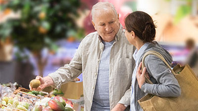 Friendly Visitors Helping Senior Man with Shopping