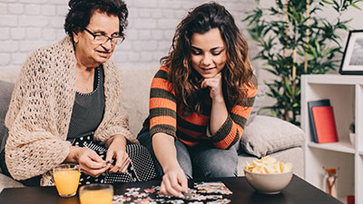 Friendly Visitors Working on Puzzle with Senior Woman